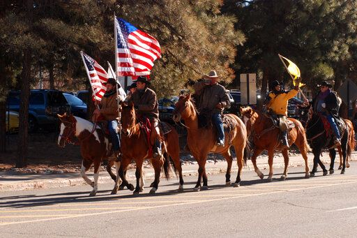 Supporters of President Donald Trump ride horses outside the Statehouse in Santa Fe, N.M., on Wednesday, Jan. 6, 2021, to protest President-elect Joe Biden's electoral victory.