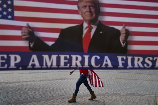 A woman draped in an American flag walks past a banner supporting President Donald Trump during a rally Wednesday, Jan. 6, 2021, in Huntington Beach, Calif.