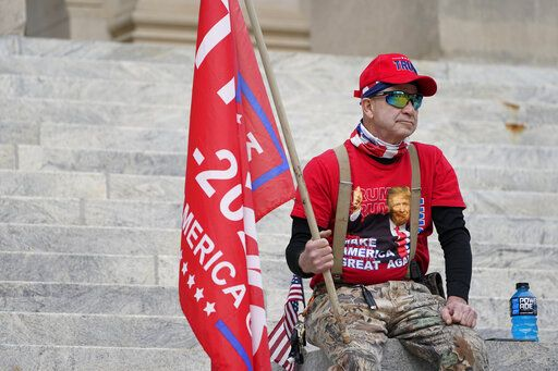An unidentified participant of a pro-Trump protest sits on the steps of the Mississippi Capitol after the small rally concluded, Wednesday, Jan. 6, 2021 in Jackson, Miss. The gathering served a dual purpose of protesting the constitutional process to affirm the president-elect's victory in the November election and to call for a revote over the state flag issue.