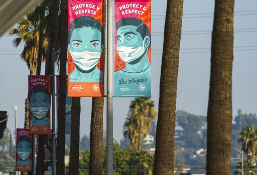 Banners advising people to wear masks against the coronavirus hang along Hollywood Boulevard in Los Angeles on Tuesday, Jan. 5, 2021. Los Angeles is the epicenter of California's surge that is expected to get worse in coming weeks when another spike is expected after people traveled or gathered for Christmas and New Year's.