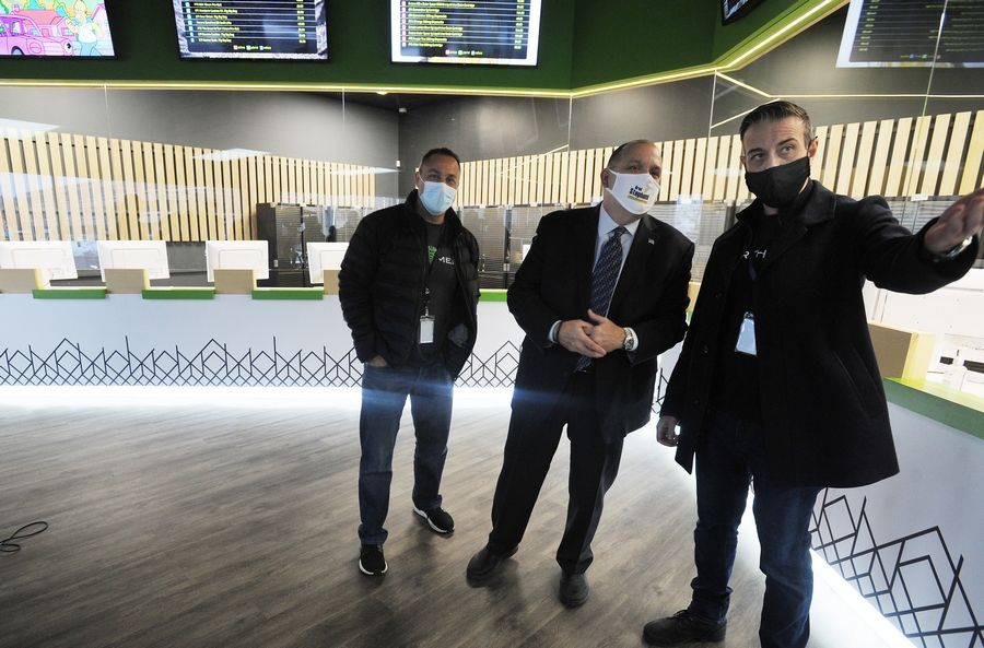 Gus Koukoutsakis, CEO of EarthMed marijuana dispensary in Rosemont, from right, shows Mayor Brad Stephens around the new store with CFO Mike Perez during a grand opening Monday morning.