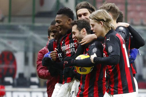 AC Milan players celebrate after defeating Torino in their Italian Cup round of 16 soccer match between AC Milan and Torino at the San Siro stadium, in Milan, Italy, Tuesday, Jan. 12, 2021.