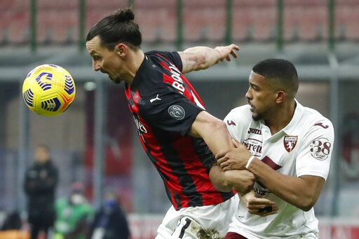 AC Milan's Zlatan Ibrahimovic, left, is challenged by Torino's Gleison Bremer during the Italian Cup round of 16 soccer match between AC Milan and Torino at the San Siro stadium, in Milan, Italy, Tuesday, Jan. 12, 2021.