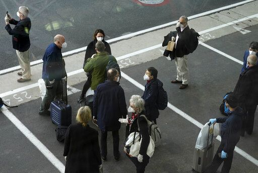 Members of the World Health Organization (WHO) team gather after arriving at the airport in Wuhan in central China's Hubei province on Thursday, Jan. 14, 2021. A global team of researchers arrived Thursday in the Chinese city where the coronavirus pandemic was first detected to conduct a politically sensitive investigation into its origins amid uncertainty about whether Beijing might try to prevent embarrassing discoveries.