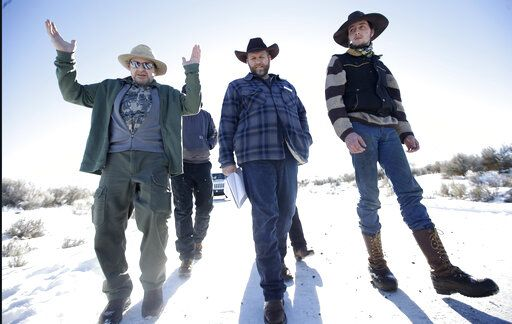 FILE - In this Jan 8, 2016, file photo, Burns resident Steve Atkins, left, talks with Ammon Bundy, center, one of the sons of Nevada rancher Cliven Bundy, following a news conference at Malheur National Wildlife Refuge near Burns, Ore. Cliven and his sons Ryan and Ammon have engaged in armed standoffs with the federal government, first in a fight over grazing permits on federal land in Nevada in 2014, and then in a 40-day occupation of the Malheur Wildlife Refuge in Oregon in 2016. Those standoffs drew the sympathies of some Western ranchers and farmers who feared they were losing the ability to prosper financially.