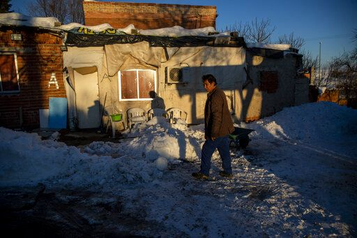 A man walks in front of his house covered with snow at the Canada Real shanty town, outside Madrid, Spain, Tuesday, Jan. 12, 2021. Ranked as one of the biggest, if not the biggest, slum areas in Europe, much of La Cañada Real has been without electricity for months now, allegedly because of power supplies being diverted to illegal marijuana plantations there. And then, the Siberia-like storm hit.