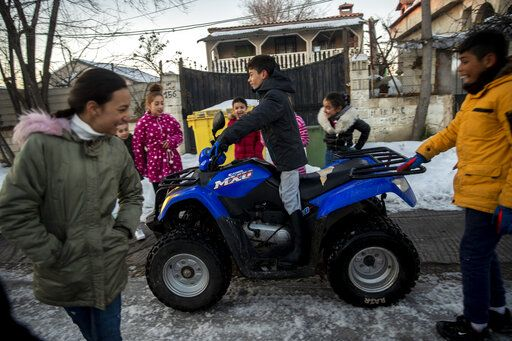 A child drives a quad at the Canada Real shanty town, outside Madrid, Spain, Tuesday, Jan. 12, 2021. An illegal informal settlement that has spread over several decades as poor Spaniards, Roma people and Moroccan migrants sought a place to live, La Cañada's poor housing and make-shift shacks stretches some 14 kilometers (9 miles) along what was once a drover's pathway on the Spanish capital's southeastern industrial outskirts. Nowadays, it's home to some 7,500 people of low or no income.