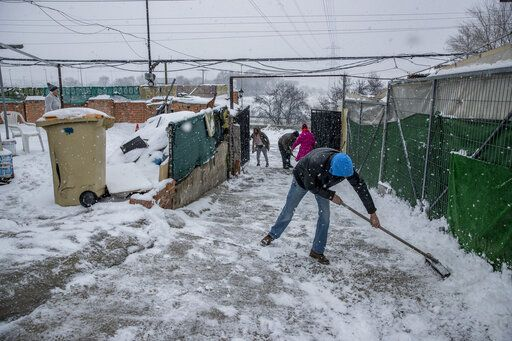 Residents clear the snow at the entrance of a house at the Canada Real shanty town, outside Madrid, Spain, Friday, Jan. 8, 2021. An illegal informal settlement that has spread over several decades as poor Spaniards, Roma people and Moroccan migrants sought a place to live, La Cañada's poor housing and make-shift shacks stretches some 14 kilometers (9 miles) along what was once a drover's pathway on the Spanish capital's southeastern industrial outskirts. Nowadays, it's home to some 7,500 people of low or no income.