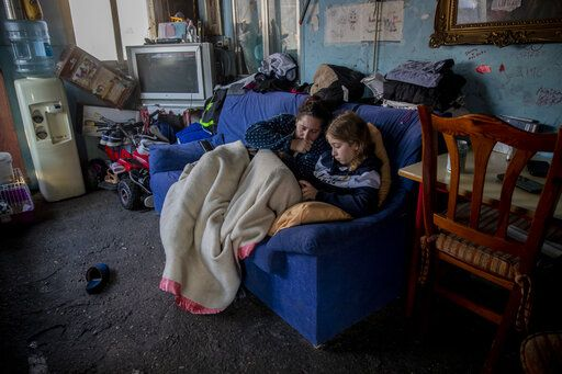A woman rests with her daughter inside their home at the Canada Real shanty town, outside Madrid, Spain, Tuesday, Jan. 12, 2021.  Shops are flimsy set-ups with little stock and the residents live off construction jobs, scrap metal collection or whatever they can, and the area has long been associated with drugs.