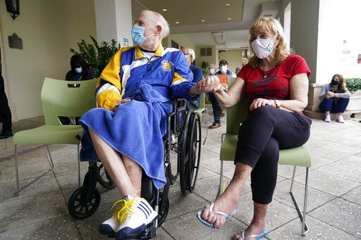 Residents Ken Fishman, 81, left, and Esther Wallach, 82, hold hands as they wait in line for the Pfizer-BioNTech COVID-19 vaccine at the The Palace assisted living facility, Tuesday, Jan. 12, 2021, in Coral Gables, Fla.