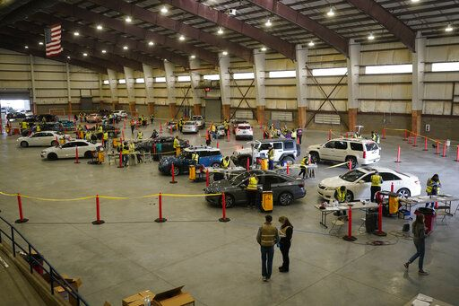 Cars pull in to nursing stations for the COVID-19 vaccine roll out at the Davis County Legacy Center Tuesday, Jan. 12, 2021, in Farmington, Utah.