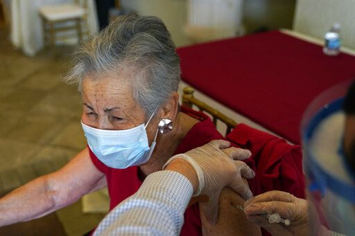 Resident Gail Nanning, 83, receives the Pfizer-BioNTech COVID-19 vaccine at the The Palace assisted living facility, Tuesday, Jan. 12, 2021, in Coral Gables, Fla.