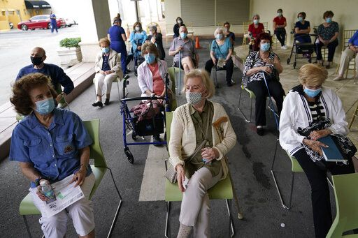 Residents wait to be cleared after receiving the Pfizer-BioNTech COVID-19 vaccine at the The Palace assisted living facility, Tuesday, Jan. 12, 2021, in Coral Gables, Fla.