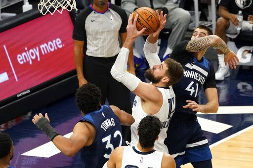 Memphis Grizzlies' Jonas Valanciunas, center, shoots past Minnesota Timberwolves' Karl-Anthony Towns (32) and Juancho Hernangomez (41) in the second half of an NBA basketball game, Wednesday, Jan. 13, 2021, in Minneapolis. The Grizzlies won 118-107. Valanciunas led the Grizzlies with 24 points.