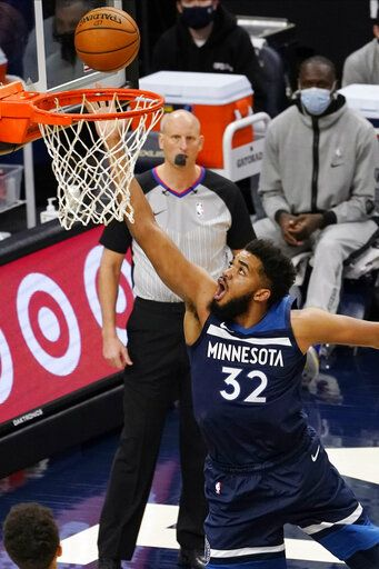 Minnesota Timberwolves' Karl-Anthony Towns (32) lays up a shot in the first half of an NBA basketball game against the Memphis Grizzlies, Wednesday, Jan. 13, 2021, in Minneapolis.
