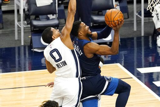 Minnesota Timberwolves' Malik Beasley, right, drives to the basket as Memphis Grizzlies' De'Anthony Melton defends in the second half of an NBA basketball game, Wednesday, Jan. 13, 2021, in Minneapolis. The Grizzlies won 118-107. Beasley led the Timberwolves with 28 points.