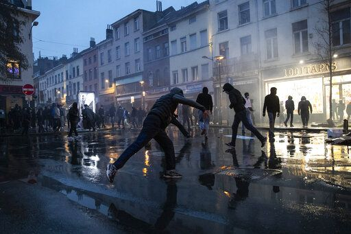 Protestors thrown stones in the Belgium capital, Brussels, Wednesday, Jan. 13, 2021, at the end of a protest asking for authorities to shed light on the circumstances surrounding the death of a 23-year-old Black man who was detained by police last week in Brussels. The demonstration in downtown Brussels was largely peaceful but was marred by incidents sparked by rioters who threw projectiles at police forces and set fires before it was dispersed.