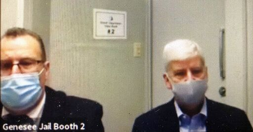 In this image taken from video, former Michigan Gov. Rick Snyder, right, with his lawyer, Brian Lennon, make an initial court appearance at Genesee County court in Flint, Mich., on two counts of willful neglect of duty in the Flint water crisis. (Genesee County court via AP)