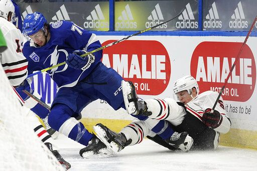 Tampa Bay Lightning center Anthony Cirelli (71) sends Chicago Blackhawks defenseman Connor Murphy (5) into the dasher with a check during the second period of an NHL hockey game Wednesday, Jan. 13, 2021, in Tampa, Fla.