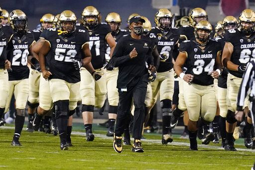 FILE - In this Nov. 7, 2020, file photo, Colorado head coach Karl Dorrell, center, leads his players onto the gridiron to host UCLA in an NCAA college football game in Boulder, Colo. Dorrell was selected as the PAC-12 coach of the year.