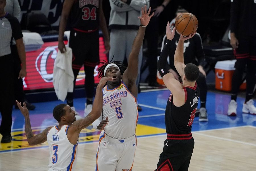 Chicago Bulls guard Zach LaVine attempts a 3-point shot over Oklahoma City Thunder guard George Hill (3) and forward Luguentz Dort (5), but misses in the closing seconds of overtime Friday in Oklahoma City.