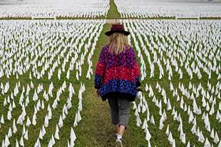 Artist Suzanne Brennan Firstenberg walks among thousands of white flags planted in remembrance of Americans who have died of COVID-19 near Robert F. Kennedy Memorial Stadium in Washington. The U.S. death toll from the coronavirus has eclipsed 400,000 in the waning hours in office for President Donald Trump.
