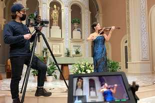 Arlington Heights native Teddy Wachholz films Irish violinist Patricia Treacy during a performance scheduled to be shown Wednesday during Joe Biden's inauguration Mass. Inauguration planners asked Treacy to have the performance filmed at Old St. Patrick's Church in Chicago in case security concerns keep her from playing in person.