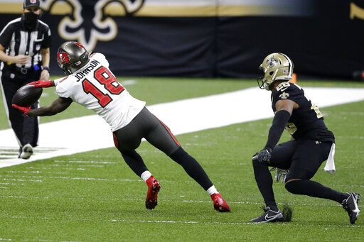 Tampa Bay Buccaneers wide receiver Tyler Johnson (18) makes the catch against New Orleans Saints free safety P.J. Williams (26) during the second half of an NFL divisional round playoff football game, Sunday, Jan. 17, 2021, in New Orleans.