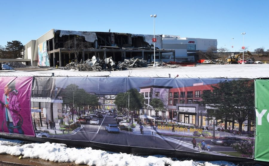 Demolition of the former Sears store at Hawthorn Mall in Vernon Hills is underway. A rendering displayed on safety fencing shows future development planned for the site.