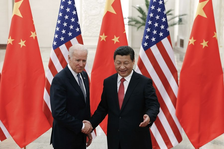 Chinese President Xi Jinping shakes hands with then U.S. Vice President Joe Biden as they pose for photos at the Great Hall of the People in Beijing.