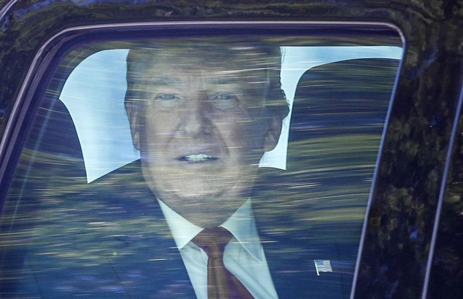 Former President Donald Trump looks out his window Wednesday as his motorcade drives through West Palm Beach, Florida, on his way to his Mar-a-Lago club in Palm Beach after arriving from Washington aboard Air Force One.