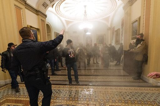FILE - In this Wednesday, Jan. 6, 2021 file photo smoke fills the walkway outside the Senate Chamber as supporters of President Donald Trump are confronted by U.S. Capitol Police officers inside the Capitol in Washington. Kevin Strong, a Federal Aviation Administration employee and QAnon follower from California who had been on the FBI's radar is facing federal charges after authorities say he confessed to taking part in the siege of the U.S. Capitol.