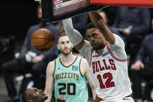 Bulls center Daniel Gafford dunks the ball over Hornets center Bismack Biyombo while forward Gordon Hayward looks on Friday in Charlotte, N.C.