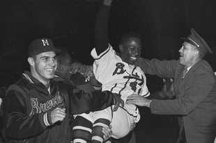 Milwaukee Braves' Hank Aaron is carried from the baseball field by teammates after they won the National League pennant with a 4-2 victory against the St. Louis Cardinals, in Milwaukee. Aaron was a legendary baseball player, but he meant even more to Milwaukee and Wisconsin.