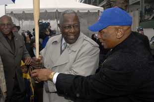 Hank Aaron gives a few pointers to Ernie Banks, right, with Billy Williams waiting his turn before the 2008 Opening Day game between the Cubs and the Braves at Wrigley Field.