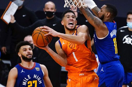 Phoenix Suns guard Devin Booker (1) drives between Denver Nuggets guard Jamal Murray and Monte Morris (11) during the second half of an NBA basketball game Friday, Jan. 22, 2021, in Phoenix.