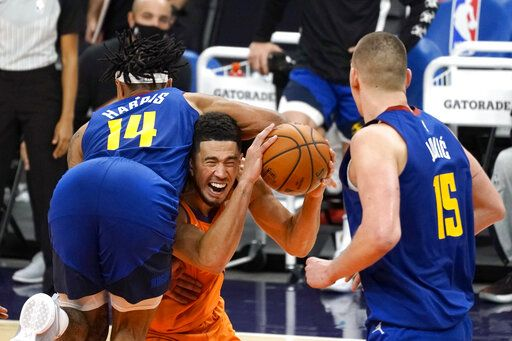 Phoenix Suns guard Devin Booker draws a foul from Denver Nuggets guard Gary Harris (14) during the second half of an NBA basketball game Friday, Jan. 22, 2021, in Phoenix.