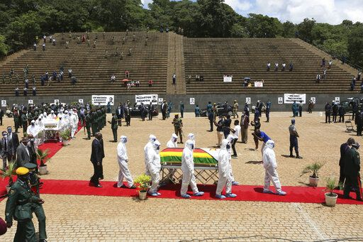 "Pallbearers carry the coffin of a government minister of Dr Ellen Gwaradzimba who died of COVID-19, at the Heroes Acre in Harare, Thursday, Jan. 21, 2021. Zimbabwean President Emmerson Mnangagwa who presided over the burial called the pandemic ""evil"" and urged people to wear masks, practice social distancing and sanitize, as cases across the country increased amid a fragile health system."