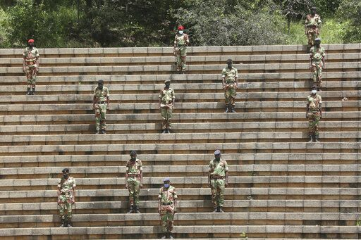 "Soldiers practice social distancing during a state burial of government ministers who died of COVID-19, in Harare, Thursday, Jan. 21, 2021. Zimbabwean President Emmerson Mnangagwa who presided over the burial called the pandemic ""evil"" and urged people to wear masks, practice social distancing and sanitize, as cases across the country increased amid a fragile health system."