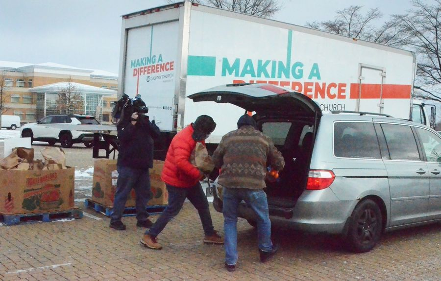 Volunteers load a vehicle during the Aurora Area Interfaith Food Pantry's first passable children's pop-up pantry in Simmons Park in Aurora.