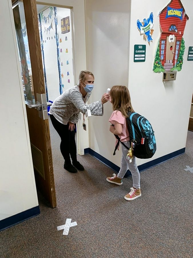 A student gets her temperature checked before starting class at Butterfield School in Libertyville Elementary District 70.