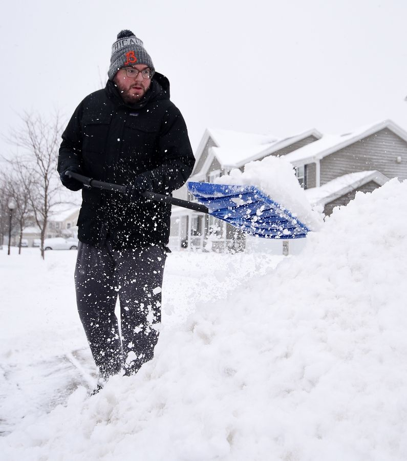 Michael Noga of Elgin shovels his driveway Tuesday morning after several inches of snow fell overnight in Elgin.