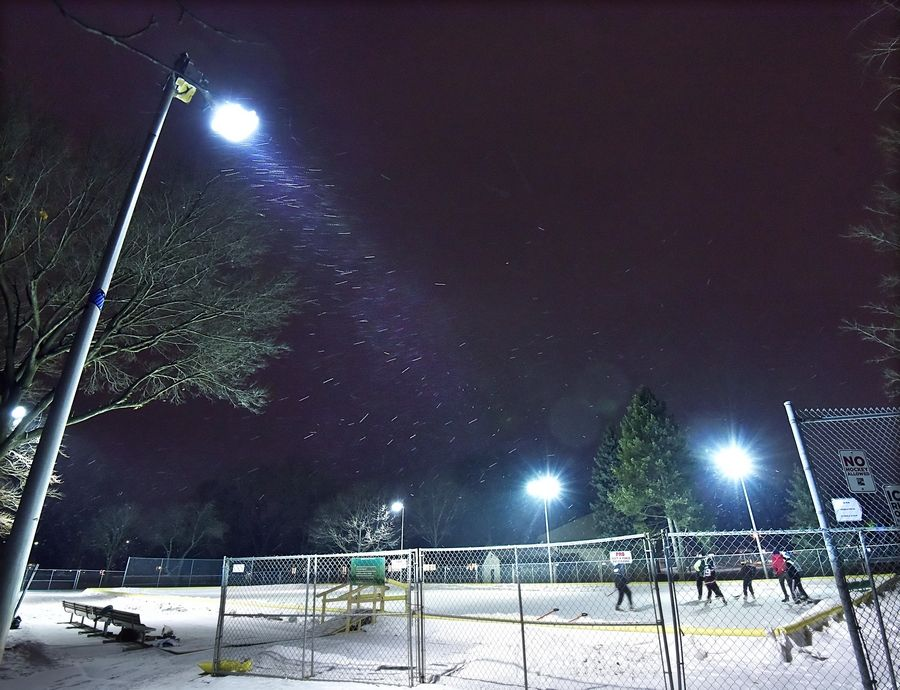 Hockey players gather in Community Park in Palatine as snow starts Monday night.