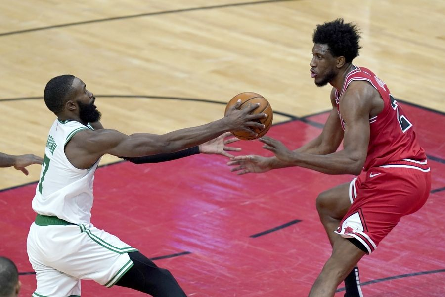 Boston Celtics' Jaylen Brown, left starts to lose control of the ball as Chicago Bulls' Thaddeus Young defends during the first half of an NBA basketball game Monday, Jan. 25, 2021, in Chicago.