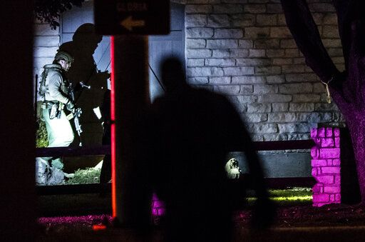 Police enter a building as they respond to hostage situation at doctor's office in Austin, Texas, Tuesday, Jan. 26, 2021. Austin police said two people were found dead after authorities made entry into the building.  (Ricardo B. Brazziell/Austin American-Statesman via AP)