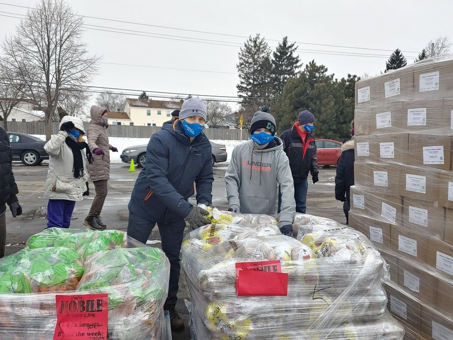 Buffalo Grove Village Manager Dane Bragg and his son Wade help out Saturday at the mobile food pantry sponsored by the Buffalo Grove Rotary Club.