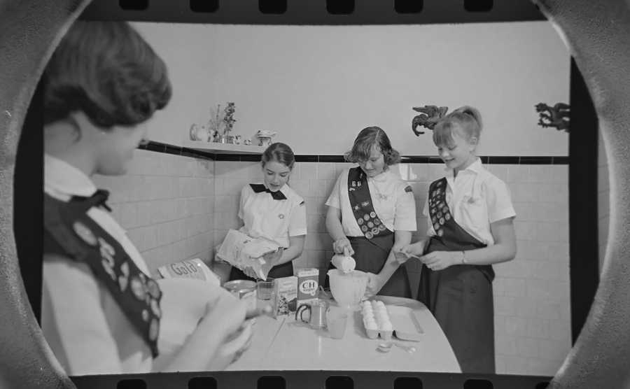 The Daily Herald Archive, Assignment # 233, Don Vickery photo: Kitchen preparations such as this are being duplicated all over the south side of Arlington Heights in February of 1965 as 34 Girl Scout troops prepare for a bake sale in the Gieseke Shoe story. Scouts pictured are from left to right are Ruth Nerlinger, Sue Pretto, Debbie Donavon and Anne Baughman.