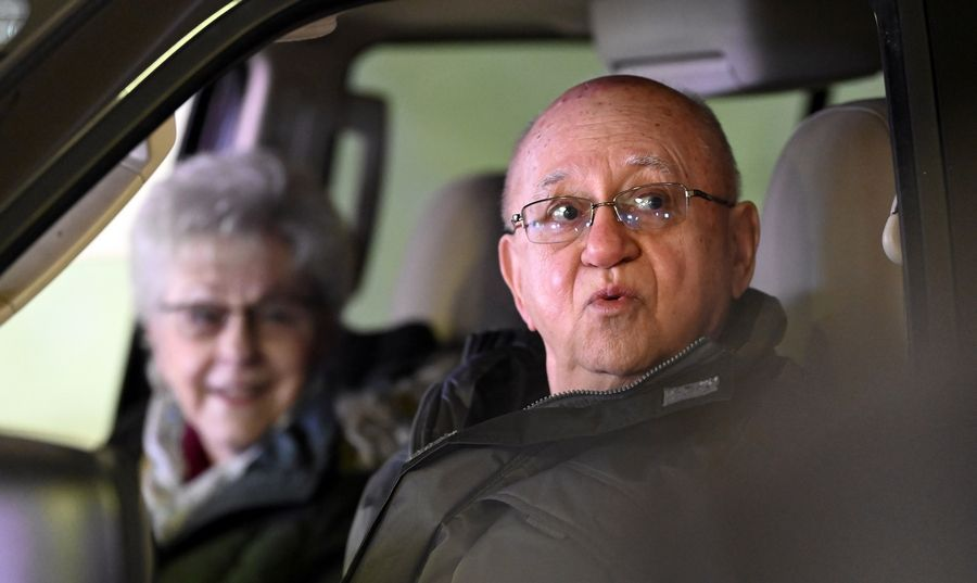 "Nick Paglia of Rolling Meadows, right, sings along to ""Let Me Call You Sweetheart"" with Lois Van Ryan of Arlington Heights, on Sunday during the Arlingtones Barbershop Chorus' drive-through Valentine's Day concert in Palatine."