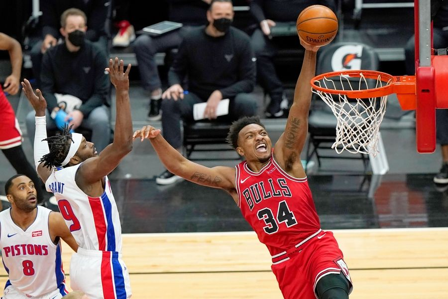 Bulls center Wendell Carter Jr., right, drives to the basket past Detroit Pistons guard Wayne Ellington, left, and forward Jerami Grant on Wednesday, Feb. 17, 2021, in Chicago. Carter was back for his second straight game after missing 11 with a right quad bruise.