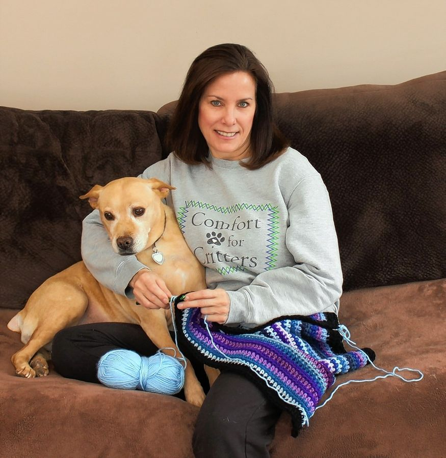 Linda Kastiel Kozlowski of Glen Ellyn sits with her dog Biscuit as she knits a blanket for the organization she started, Comfort for Critters.